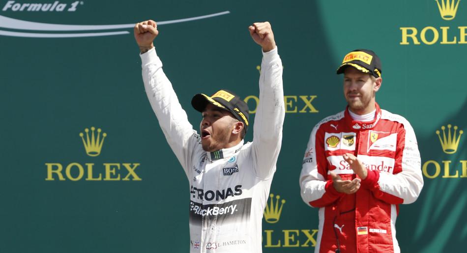 Formula One - F1 - British Grand Prix 2015 - Silverstone, England - 5/7/15 Mercedes' Lewis Hamilton celebrates his win on the podium with Ferrari's Sebastian Vettel (R) Reuters / Phil Noble
