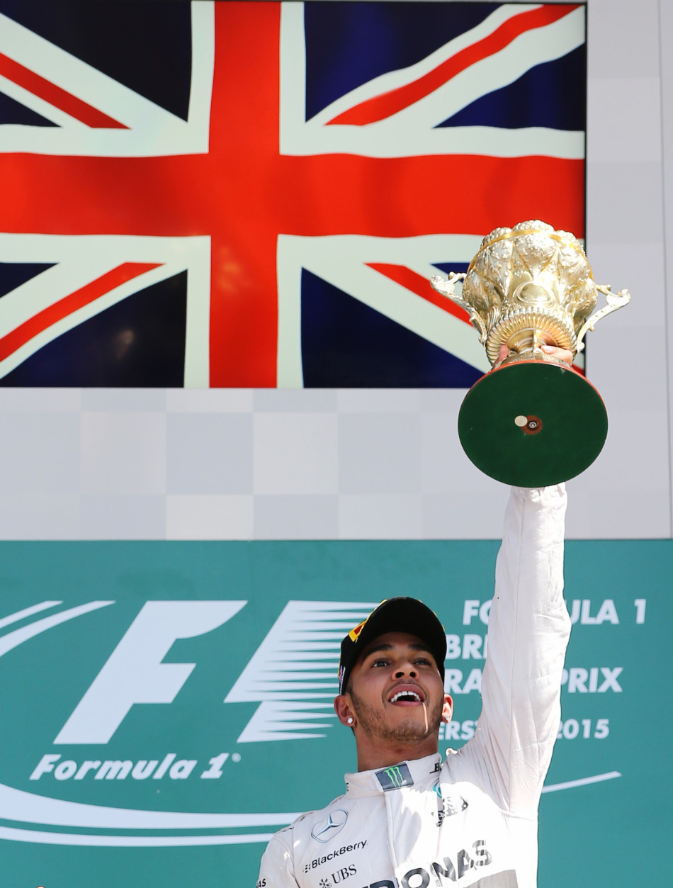 Formula One - F1 - British Grand Prix 2015 - Silverstone, England - 5/7/15 Mercedes' Lewis Hamilton celebrates his win on the podium with the trophy Reuters / Paul Childs